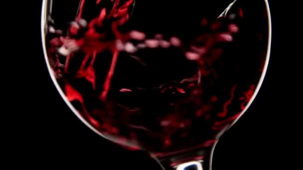 Rotwein gießen, Zeitlupe. Wein in Glas gießen. Silhouettenaufnahme mit schwarzem Hintergrund.