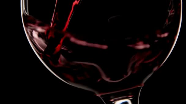 Červené víno se nalévá do skla makro záběr zblízka. Silueta s černým pozadím