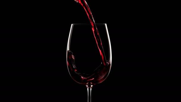 Nalil do sklenice na víno červené víno. Silueta Zpomalený pohyb. Černý backgroung, kontrast světla.