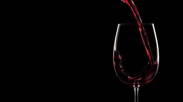 Červené víno se nalévá do skla. Zpomalený pohyb, silueta