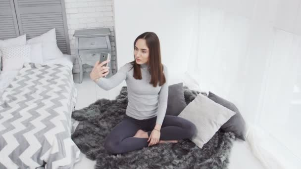 Caucasian female (girl, woman) using phone for self portrait (selfie). White room with window and teddy bear.