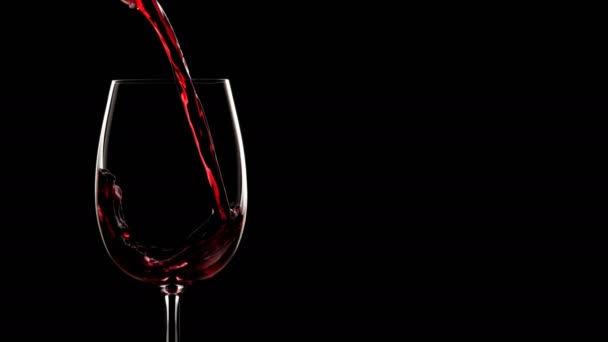 Červené víno se nalévá do skla. Víno a sklo silueta na černém pozadí izolované