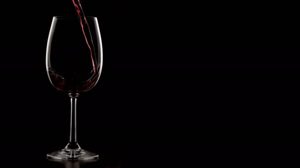 Silhouette shot of pouring wine in wine glass. Dark room with isolated background.