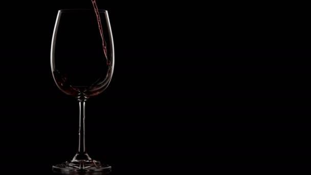 Silhouettenaufnahme vom Einschenken von Wein in Weingläser. Dunkler Raum mit isoliertem Hintergrund.