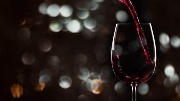 Červené víno nalévá do sklenice 4K. Zpomalený pohyb, vánoční pozadí