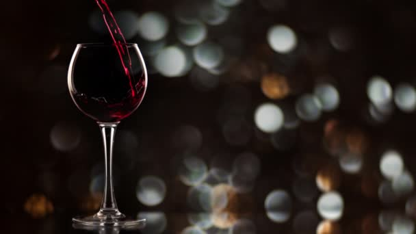 Wine pouring into glass in slow motion. New year bokeh background