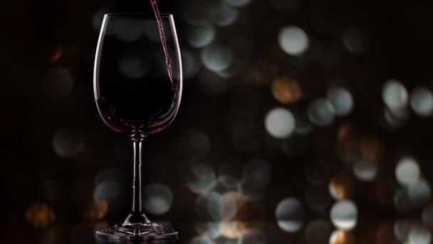 Novoroční oslava. Červené víno tekoucí do skla, zpomalené
