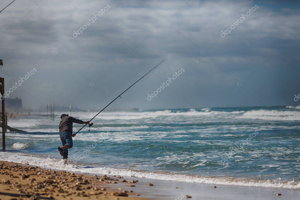 Elderly man fishing with a fishing rod on the beach in Akre, Israel