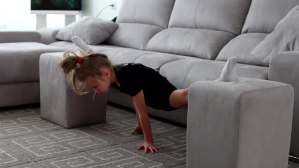 Malá roztomilá holka doma cvičí gymnastiku. Online školení. Protahování, motouzy