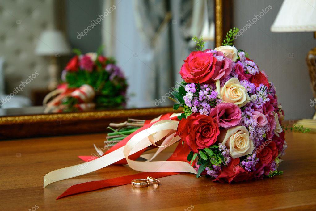 dos anillos de oro de la boda ramo de novia con rosas rojas y ...