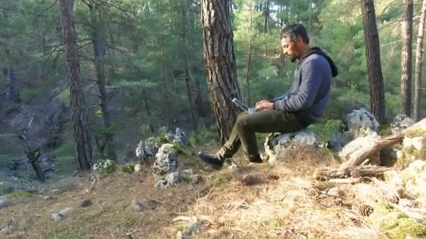 Mann arbeitet mit Laptop an Baum im Naturpark