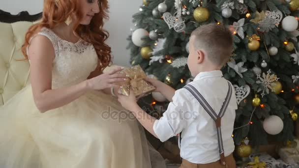 young mother and son consider Christmas gifts on the background of ...
