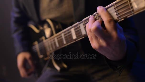 Mann sitzt und spielt Gitarre in einem dunklen Raum