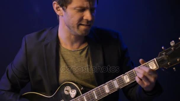 ein Mann spielt E-Gitarre und singt in einem dunklen Raum