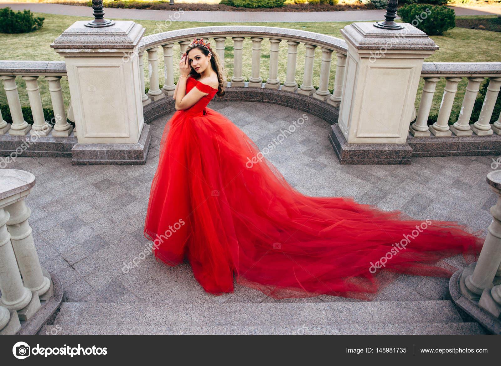 bf51e2174c18 Bella donna in un vestito rosso lussuoso con un lungo strascico– immagine  stock