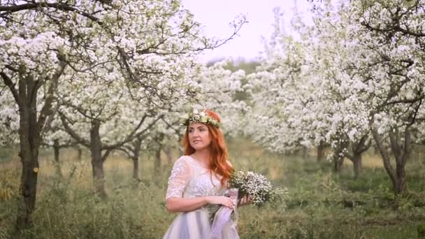 Red-haired beautiful woman in a luxurious dress and with a wreath on her head is standing in a flowering garden