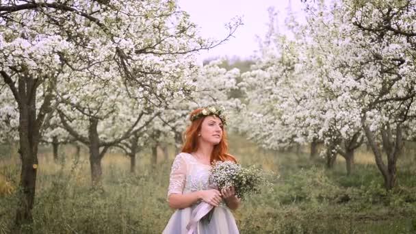 Krásná Rudovláska v luxusních šatech a s věncem na hlavě stojí v kvetoucí zahradě