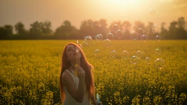 Mladá žena vlasy foukat bubliny na kameru venku v letní louka