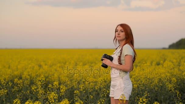 Fiatal nő fotós egy virágzó mező
