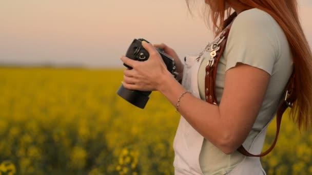 Fotograf mladá žena držící fotoaparát, detail