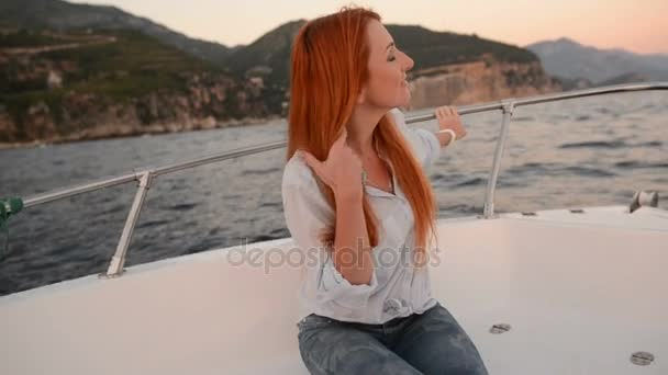 young woman sitting in going cutter looks at adriatic sea