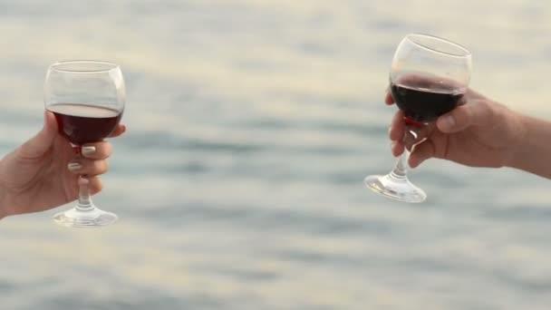 milenecké dvojice clink brýle s červeným vínem na pozadí moře