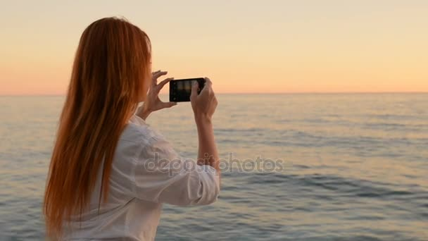 Young woman is photographing on the phone camera sea landscape