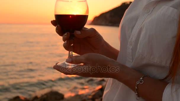 Mladá žena drží sklenku červeného vína, západ slunce u moře