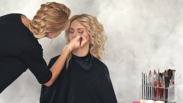 Make-up artist puts eye shadow in the beauty salon