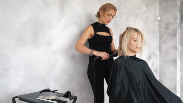 The hairdresser makes curls using a curling iron, slow motion