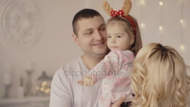 malá holčička se hraje s její mámou a tátou u vánočního stromu