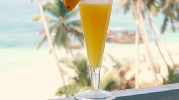 alkoholfreier Ananascocktail im Glas vor tropischem Strandhintergrund