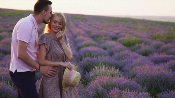 junges romantisches Paar umarmt sich in einem blühenden Lavendelfeld.