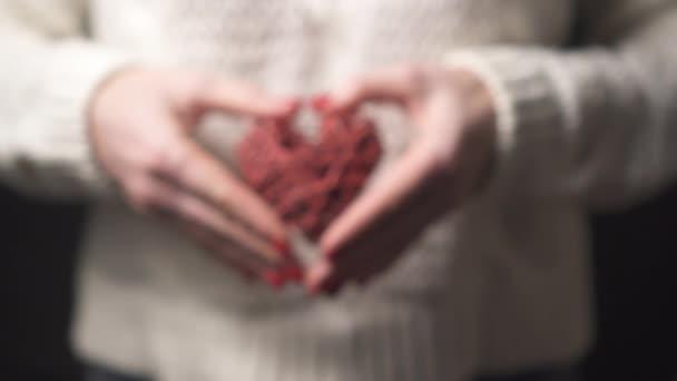 Detailní záběr ženské ruce drží ozdobné srdce, selektivní zaměření.