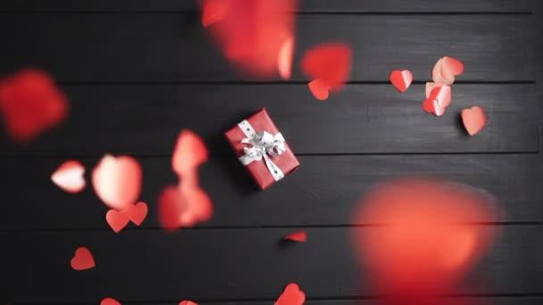Mnoho rudých srdcí padá na stůl, na kterém leží krabice s dárkem.