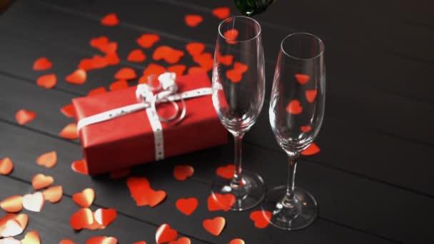 Šampaňské je naplněno do sklenice na černém stole poblíž dárkové krabice.