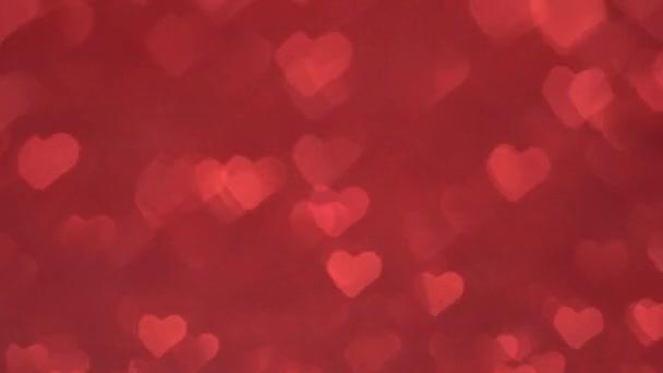 Bokeh ve tvaru srdce se pohybuje cyklicky na červeném pozadí.