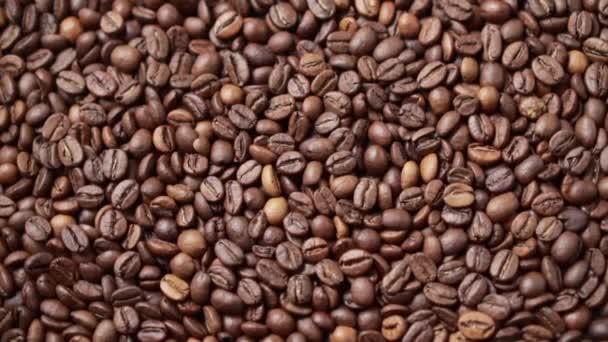 Tmavá pražená kávová zrna se pohybují v kruhu.