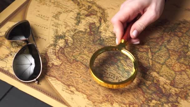 Examining the map with a magnifying glass, close up.