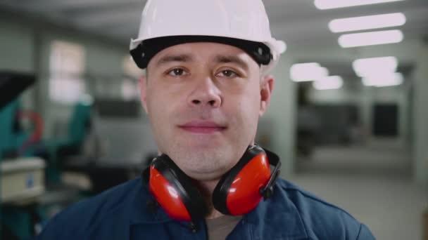 Lächelnder männlicher Fabrikarbeiter zeigt Daumen hoch.