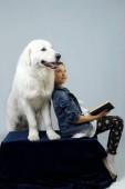 Domácí zvířata, zvířata den, lidé koncept. Dívka si hraje s psíkem. Dívka s knihou za její Pet.Young dívka a velkého bílého psa