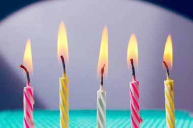 Colorful festive burning candles, cropped shot. Holidays, Birthday concept. Abstract colorful background.