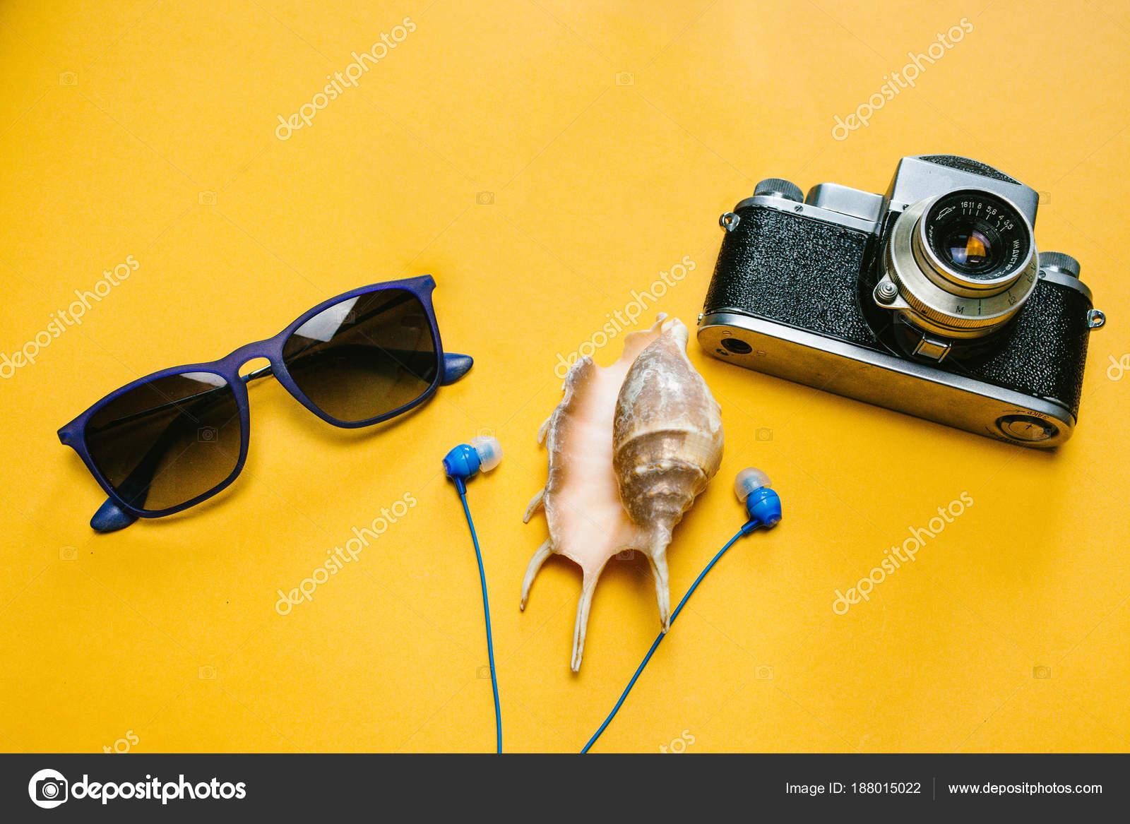 1270c5d4722f6 Acessórios de um viajante em um fundo amarelo com óculos de sol ...