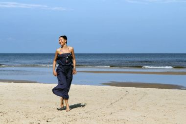 Baltic sea, woman walking on beach in dress