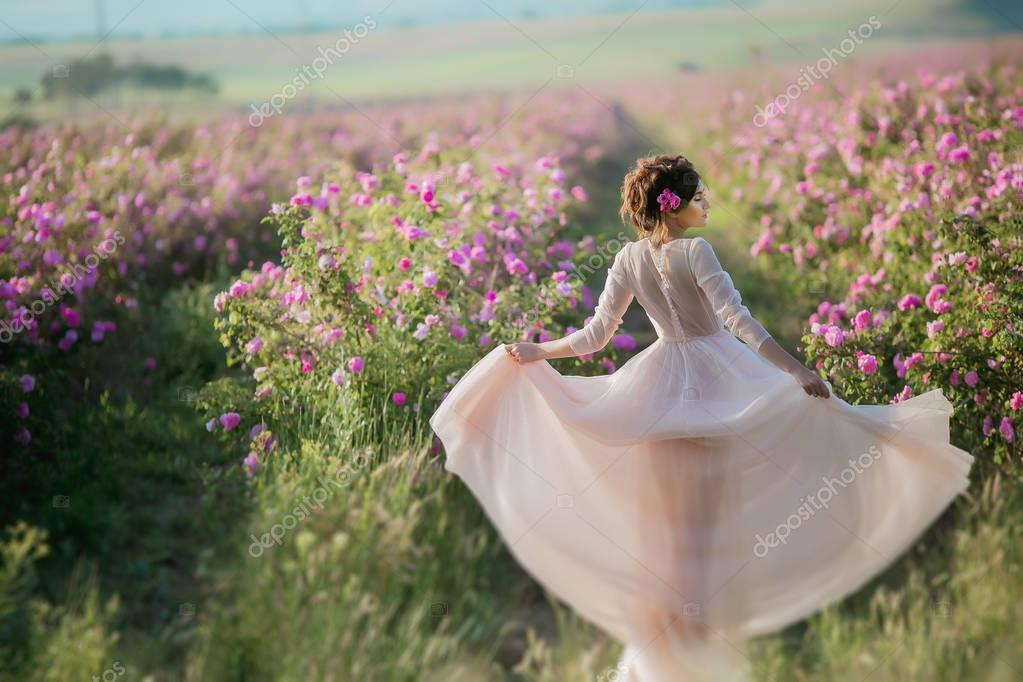 young beautiful female model in long dress with floral wreath on head posing on nature background