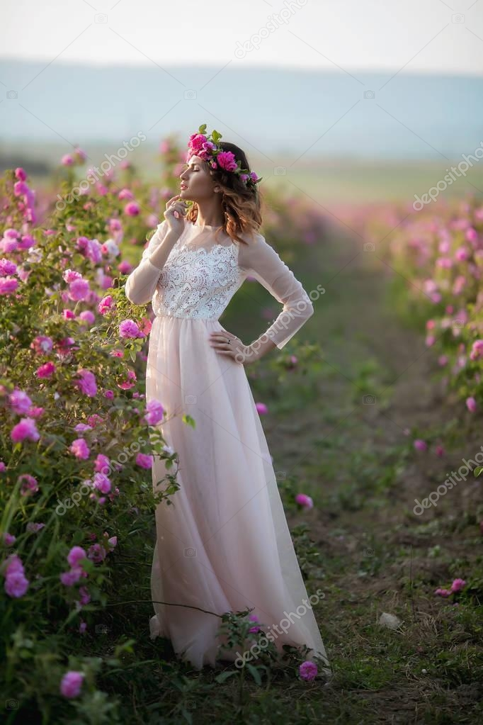 woman in long dress and floral wreath standing on green nature background