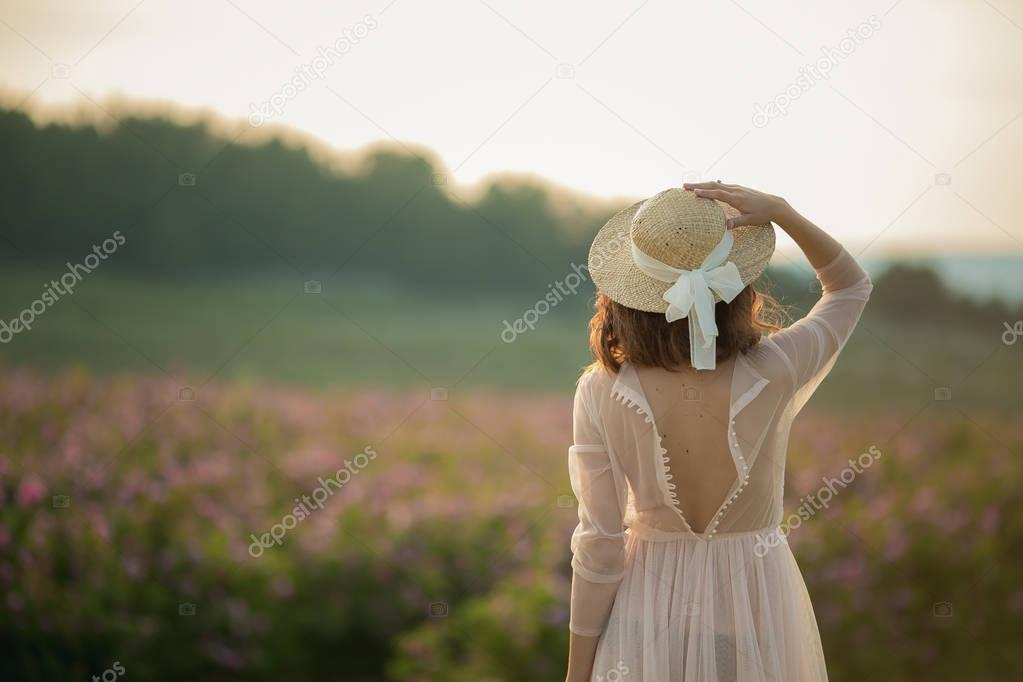 woman in long dress and straw hat standing on green nature background, back view