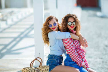 two attractive women with red lips hugging sitting on beach in sunglasses