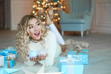 beautiful young blonde woman posing in studio with Christmas decorations