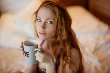 beautiful red haired woman drinking coffee